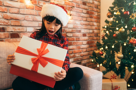 Christmas girl kid in a Santa hat opening mouth. cute child open gift box with red ribbon at home. decorated christmas tree in the living room. Stock Photo