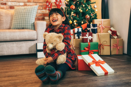 Christmas girl in a Santa hat very surprised and excited. little child smile with bid tooth sitting on the floor in living room. kid with deer on head holding teddy bear doll at home in christmas.