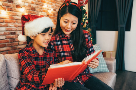 Parent and little child having fun near Christmas tree indoors. young mother and cute girl reading christmas poems together. family with cute deer and santa hat at home. 스톡 콘텐츠