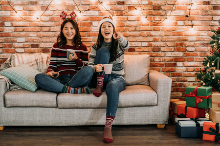 friends watching comedy at home on christmas eve. young girl laughing pointing at the television. comfortable sitting on sofa in xmas holidays lifestyle.