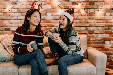 young girls chatting and having fun at home. relaxing celebrating xmas holiday concept. best friends with santa hat and deer cheerful laughing. Stock Photo
