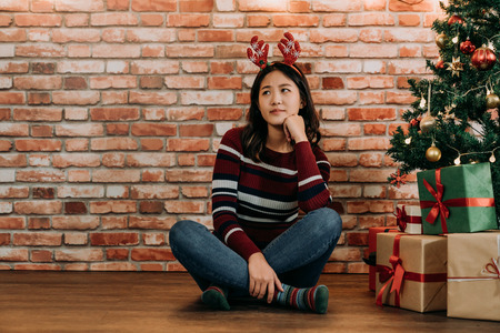 disappoint girl sitting at home alone near the Christmas tree. young girl hasn't be invited to any Xmas party on Christmas eve. teenager concerned about the xmas gifts for friends. Stock Photo - 113379074