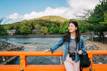 elegant asian traveler relying on the handrail on the bridge and enjoy the view. Japan vacation travel woman relaxing above the river. sightseeing in wonderful weather in Kyoto.