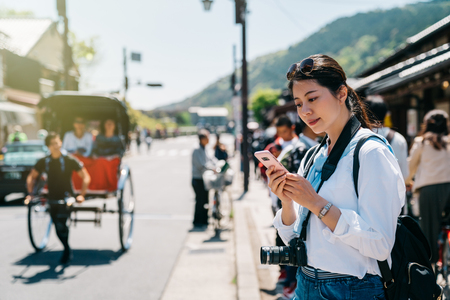 elegant girl photographer standing on the road and using cellphone while a pulled rickshasw walking past. crowd walking on the teeming street. Japanese people lifestyle.