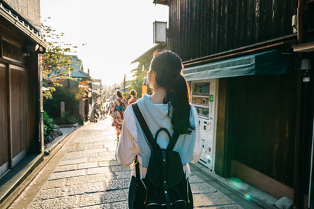 back view of beautiful lady walking on the street and in front her are two young girls walking with kimono. Japanese lady with colorful traditional costume concept. asian travel alone in kyoto tour. Banco de Imagens