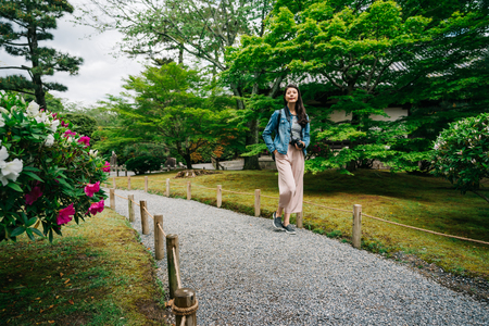 full length photo of an elegant female traveler walking on the path in the green garden. lady lens man visiting Kyoto Japan. Young girl love nature life, travel, freedom.