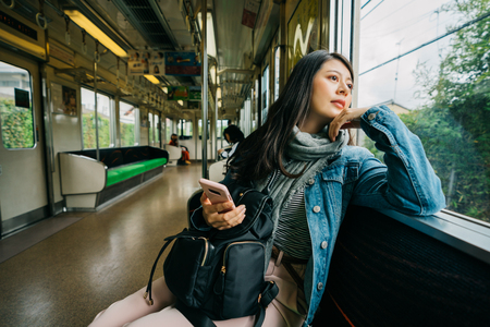 elegant lady relying on the window and curiously looking outside the view in the metro. Happy commuter enjoying train travel to go to work in the morning.  Asian woman enjoying view passing by.