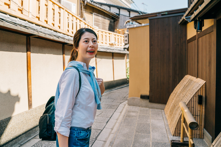 young backpacker walking in the alley with Japanese wooden building surrounding. Japan travel tourist woman on vacation in Kyoto. tourist enjoy peaceful sightseeing spot.