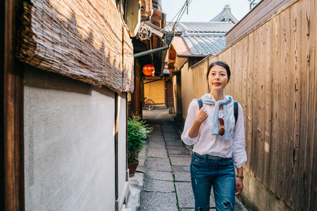 elegant female traveler is walking in the Japanese traditional alley and looking into the wooden house. young tourist following japan travel guide visiting the town in Kyoto.