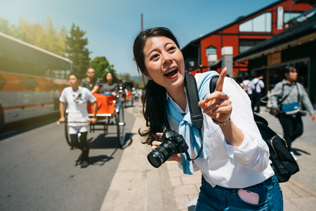 joyful girl traveler curiously pointing to the sky with a rickshaw in the background. lady lens man having fun in trip to Japan. travel in Kyoto lifestyle.