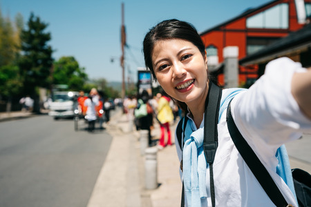 elegant girl traveler standing on the busy road and taking selfie in Japan. Travel Vacation Tourist Selfie in town in Kyoto. asian girl on summer vacation visiting famous tourist destination. Stock fotó