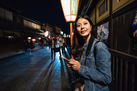 beautiful female tourist waiting alone on the path for her local friend to have dinner together. young lady standing outside the sushi store in Hanamikoji Dori. Japan travel tourist woman on holiday.