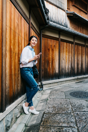 pretty lady relying on the wooden wall and waiting for her boyfriend coming. Japanese elegant young girl lifestyle. woman playing online game app on smartphone. Stock Photo