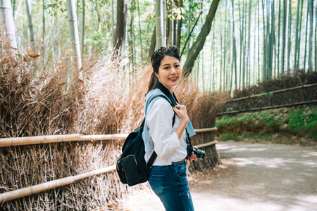 beautiful tourist with sunglasses walking in the bamboo grove and turning back while her boyfriend calling her. Travel Japan summer holiday girl enjoying. tourist in Kyoto lifestyle. Stok Fotoğraf