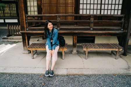 asian traveler sitting on the bench in front of the Japanese temple which built by the wood. Tourist on Asia travel looking at the view sitting relaxing on wooden chair. backpacker lifestyle. 免版税图像