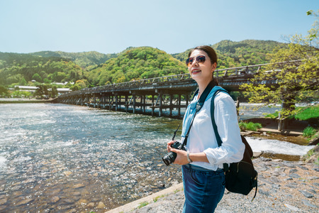 elegant girl traveler standing next to the clean river and see the beautiful view. elegant woman enjoy the beauty ofthe blue sky in kyoto trip in Japan. backpacker travel lifestyle.