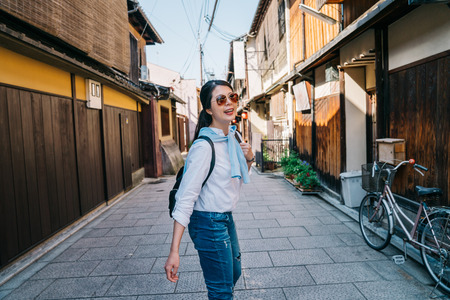 attractive lady joyfully walking in the street and turning back to make sure her boyfriend is following her. Travel Japan summer holiday girl enjoying peaceful town. finding the famous things to see in kyoto. Imagens - 113395175