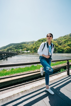 full length photo of elegant traveler carrying camera and relaxing next to the river in Kyoto. travel tourist in Japan concept. Girl on summer holiday having fun sitting on handrail.