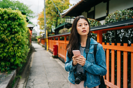 female tourist using cellphone to search the next sightseeing spot. Tourist in Asia walking on famous Japanese destination. Asian girl using cellphone camera app in Kyoto.