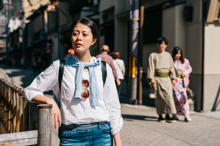 attractive lady relying on the handrail and already waits for her friend for a long time. dating Japanese boy and girl wearing traditional kimono walking by. Japanese young people lifestyle.