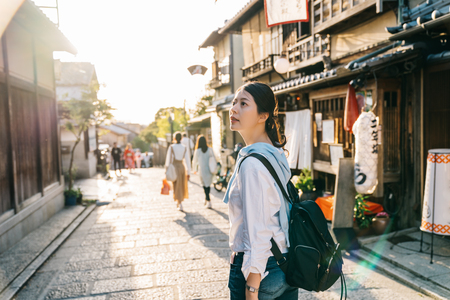 traveler stopped on the street and looking at the Japanese traditional building. Japan travel tourist woman on vacation in Kyoto shopping in alley. cheerfully visit kyoto. Standard-Bild - 112552808