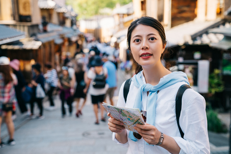 female tourist holding the map and standing on the lively street in Japan. traveler finding direction on paper guide in japan holidays. foreigner backpackers visiting teeming town in Kyoto. 스톡 콘텐츠