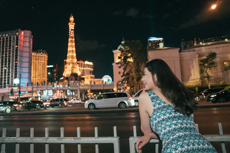 elegant asian woman enjoying the beauty of the night las vegas, US. young girl relying on the handrail looking at the busy road with traffic. eiffel tower standing in the dark sky shining with lights.