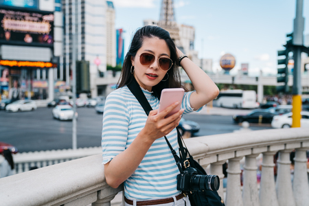 beautiful lady flicks her standing in the busy city and using cellphone chatting. Young photographer using photo graphing app on cellphone ready to take selfie. travel in America on sunny day.