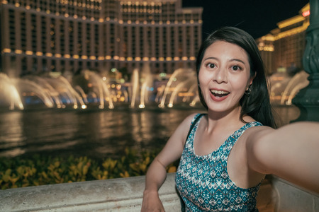 Asian woman in dress taking selfie photo with fountain water show in front the hotel in las vegas. young girl night out lifestyle. fashion lady face to camera smiling at night.