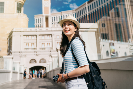beautiful tourist is walking and going to join the guide tour in museum. travel photographer enjoying the beauty of the blue sky in city surrounding skyscrapers. finding las vegas hotels to stay.