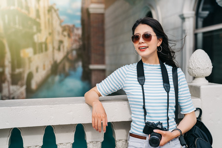 beautiful photographer traveling in Europe and relaxing on the bridge. travel lens man having trip in Italy concept. young Asian lady enjoying holiday near the canal.
