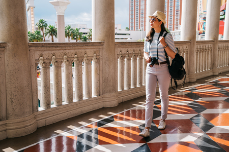 tourist walking in the passageway of a white classic building. famous tour spot in Las Vegas. femal lens man sightseeing from hotel passageway.