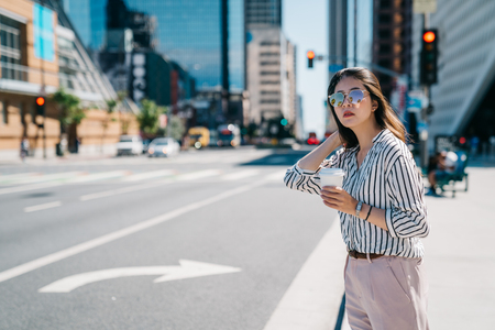 female worker standing in the city center. young office lady in shirts waiting taxi cab beside the road. businesswoman holding coffee going home after work.