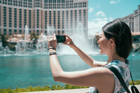 young girl traveler using photography app to take pictures of the amazing fountain in front the hotel in las vegas. woman tourist having fun traveling outdoors during holidays in USA.