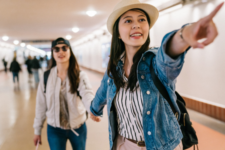 female tourists found the platform and excited pointing to the sign in Union station in America. Women girlfriends traveling in America smiling joyful having fun in sightseeing trip. Stock Photo