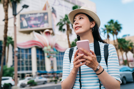 traveler walking on the street in Las Vegas and finding the way to casino. young lady hobby is a gambler using online map app cellphone to get the right direction. famous sightseeing spot in vegas.