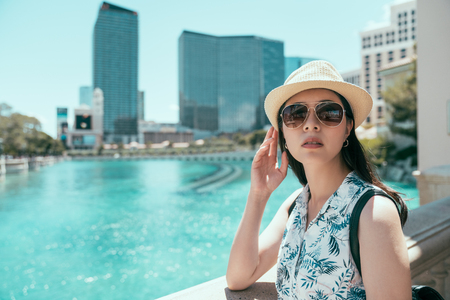 asian girl with hat and sunglasses standing on the balcony in las vegas travel in holiday. clean blue water in the big pond in city center in vegas. skyscrapers in the blue sunny sky. Stock Photo