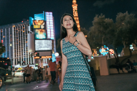Urban city Asian young girl walking on street at night. shopping district with tall light buildings in background. american people night lifestyle.
