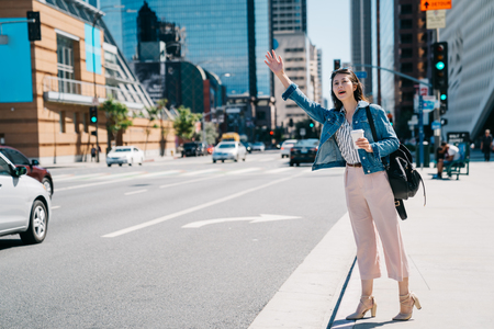 full length photo of beautiful woman beckoning the bus in the busy city. young office lady calling taxi cab in Los angeles, holding coffee standing in street of LA, USA.