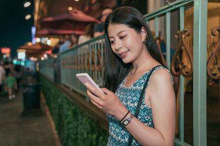 young asian girl relying outside the restaurant on the street in las vegas. elegant lady using using cellphone texting sms message. attractive woman nightlife in USA. Stock Photo
