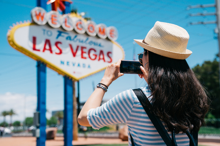 pretty tourist taking photo of the Las Vegas city sign by cellphone. young lady traveler shooting the famous landmark in Nevada. backpacker in las vegas trips concept.