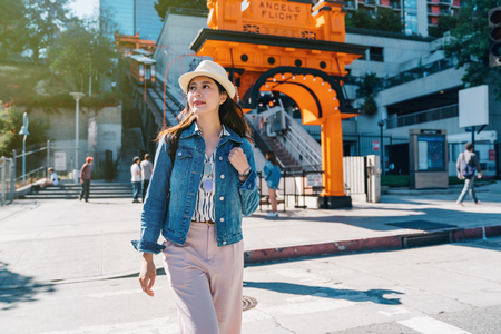 female traveler going to visit the city after taking the railcar. Portrait of beautiful smiling happy young lady tourist walking outside in City of Los Angeles. Traveling tour in USA. Stock Photo