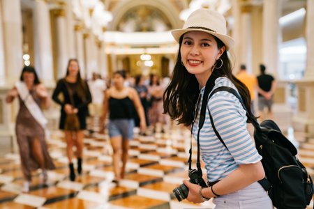 beautiful traveler cheerfully walking in the shopping mall and face to camera smiling. woman tourist standing in department store indoor. lady backpacker visit the famous shopping center in LA.