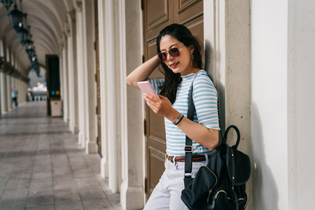 pretty college girl waiting her friend on the passageway after the course. Student lady outdoor in balcony smiling happy going back to home. teenager using communicate app chatting on cellphone. Stock Photo