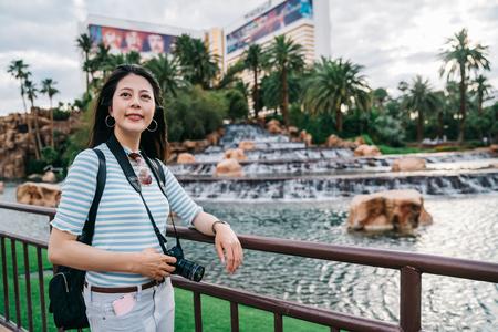 attractive lady standing near the pool and relaxing arm on the handrail. young traveler enjoying the beauty of the blue sky in las vegas. traveler having vegas vacation in holiday.