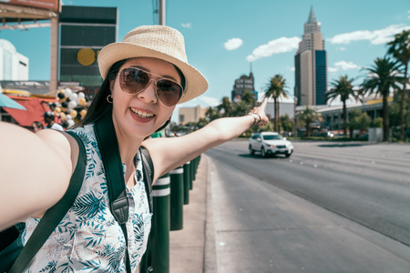 happy young girl tourist smiling taking self-portrait picture on the city center. traveler with hat and sunglasses pointing to the tallest building in Las vegas on sunny day. travel woman lifestyle.