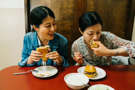 hungry ladies sitting in the red table and joyfully eating hamburgers. Asian sisters having lunch at food stand. Young urban woman enjoying meal at restaurant table with friend in city. 写真素材