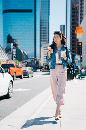 Bürodame, die Kaffee und Handy hält und auf der Straße zur Arbeit geht. frischer Absolvent begann im Stadtzentrum von LA zu arbeiten. Lebensstil der jungen Arbeitnehmerin.
