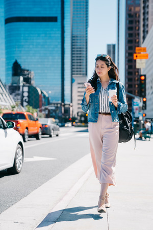office lady holding coffee and cellphone, walking on the street to work. fresh graduate started working in the city center in LA. Young female worker lifestyle. Archivio Fotografico