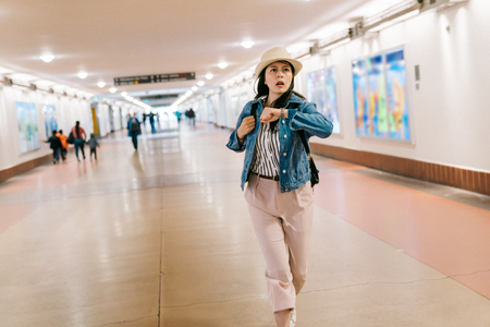 beautiful lady trying to catch the train and looking at her watch. Young woman hurry up and running in the corridor in Union station in LA. attractive girl in rush concept. Фото со стока